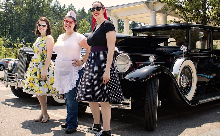 """Cedar Sinai Park Life Enrichment Team members, from left, Phoenix Barrow, Heather Sprinkle and Sarah Whisenhunt pose in front of one of the classic cars on display launching the """"Through the Decades"""" Rose Festival celebration at CSP."""